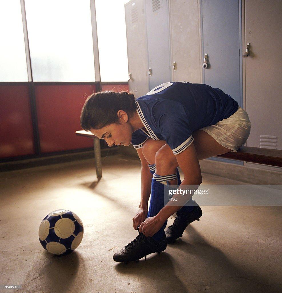 Soccer player tying cleats in locker room : Foto de stock