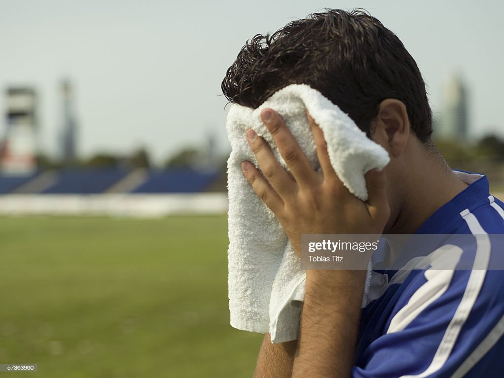 A soccer player wiping his face with a towel : Stock Photo