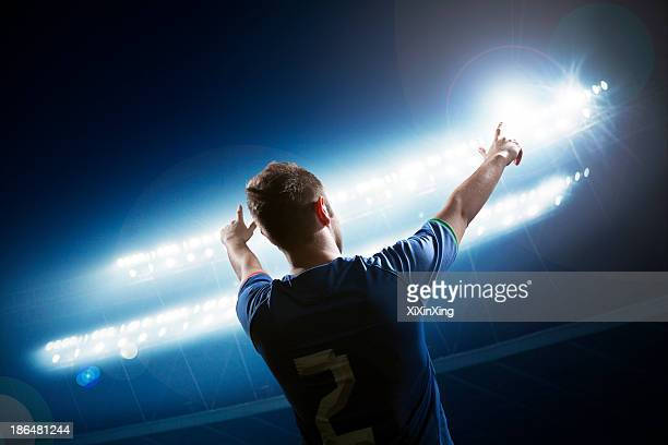 soccer player with arms raised cheering, stadium at night time - traje de fútbol fotografías e imágenes de stock