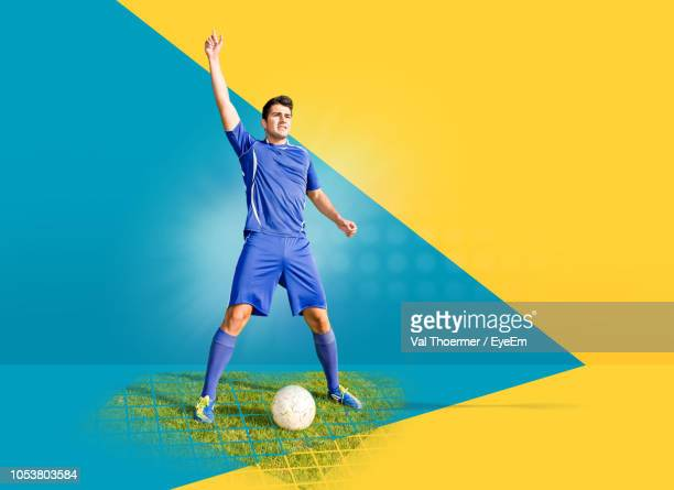 soccer player with ball standing against colored background - サッカーユニフォーム ストックフォトと画像