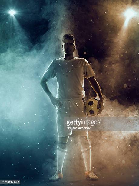 soccer player with ball standing under two-color spotlights - football strip stock pictures, royalty-free photos & images