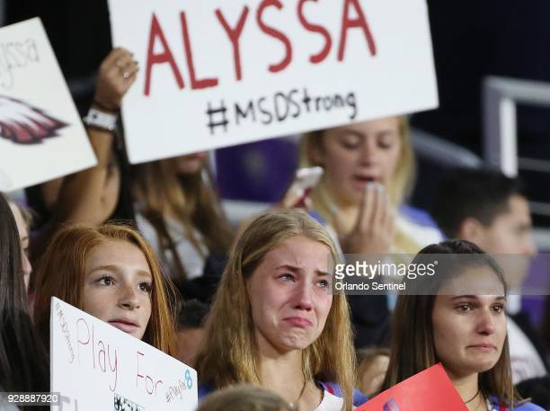 Soccer players and other students from Marjory Stoneman Douglas High School hold signs and wear the jersey of their former teammate Alyssa Alhadeff...
