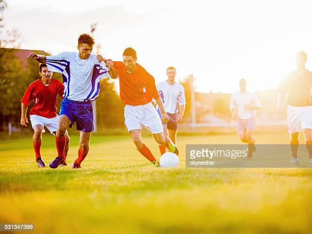 Joueurs de football au coucher du soleil.