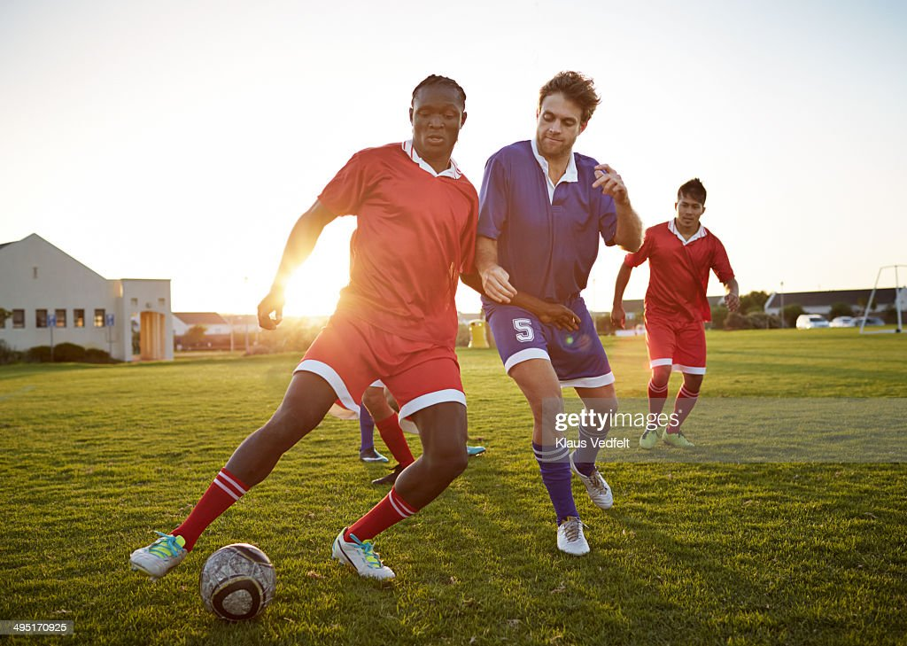 Soccer players battling to get the ball : Stock Photo
