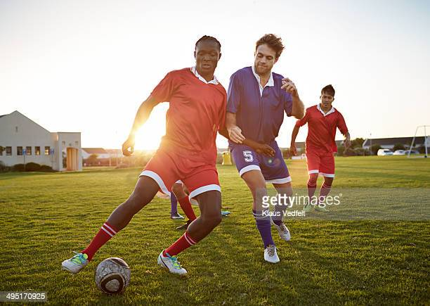 soccer players battling to get the ball - fußballspieler stock-fotos und bilder