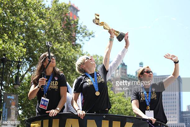 Soccer players Carli Lloyd, Megan Rapinoe, holding trophy, and head coach Jill Ellis ride a float during a Ticker Tape Parade for World Cup Champions...