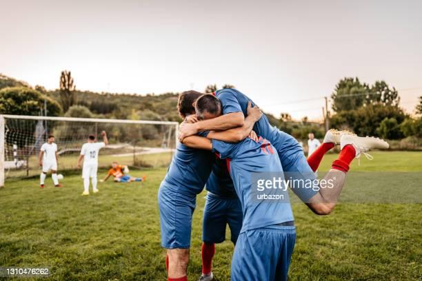fußballer feiern ein tor - punkten stock-fotos und bilder