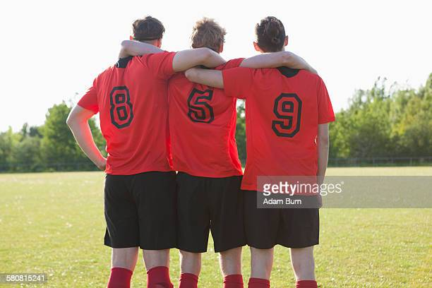 soccer players celebrating on field - fußballtrikot stock-fotos und bilder