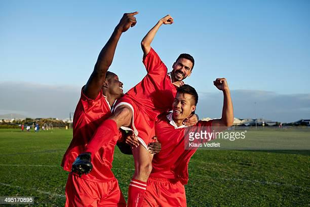 soccer players cheering after goal - mannschaftssport stock-fotos und bilder
