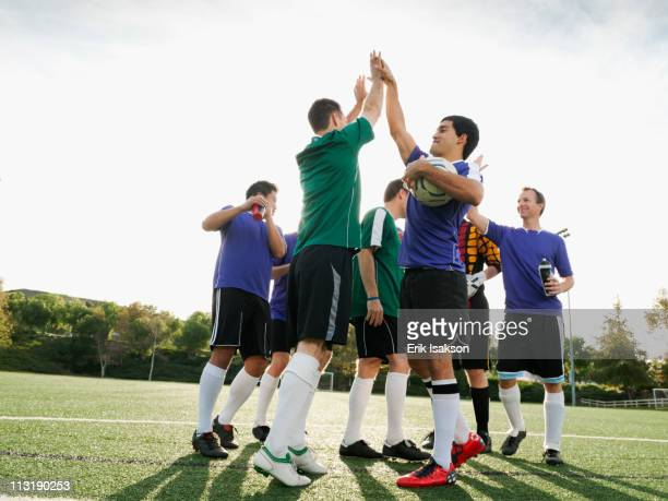 Soccer players cheering on soccer field