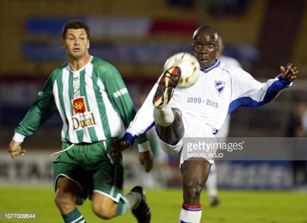 Soccer players Claudio Baggio and Angbwa Benoit are seen fighting for the ball in Montevideo Uruguay 01 April 2003 Angbwa Benoit de Nacional despeja...
