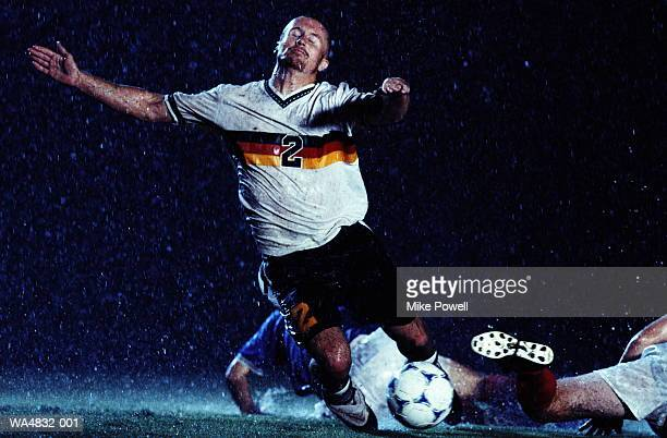 soccer players fighting for ball in rain at night - sportlicher zweikampf stock-fotos und bilder
