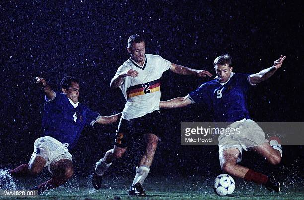 soccer players fighting over ball - sportlicher zweikampf stock-fotos und bilder