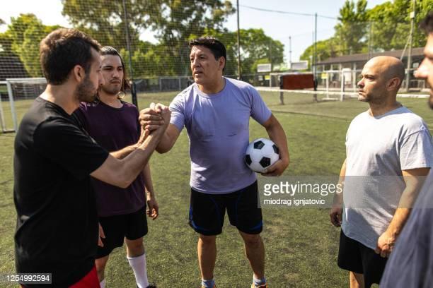 jugadores de fútbol saludando a los jugadores del equipo oponente antes del inicio del partido - capitán del equipo fotografías e imágenes de stock