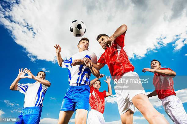 Soccer players heading a ball against the sky.