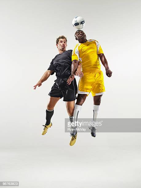 2 soccer players heading the ball