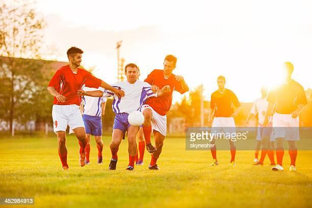 Joueurs de football en action au coucher du soleil.