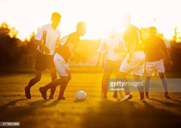 Soccer players in action at sunset.