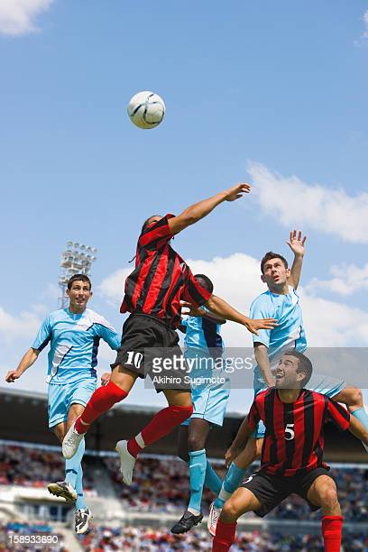 soccer players jumping for header - fußballstürmer stock-fotos und bilder