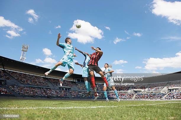 soccer players jumping for header - atacante de futebol imagens e fotografias de stock