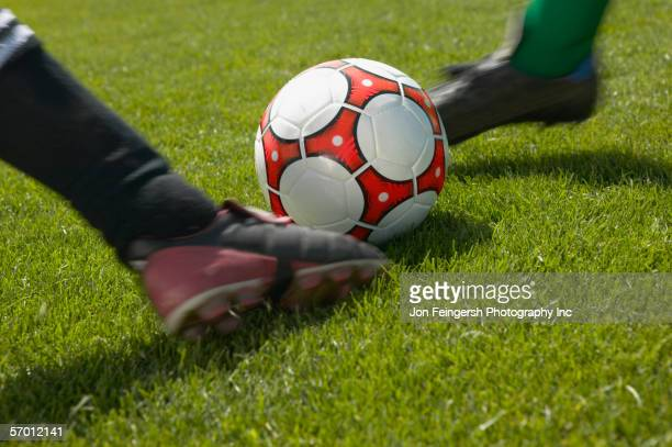 soccer players kicking the ball simultaneously - defender soccer player stock photos and pictures