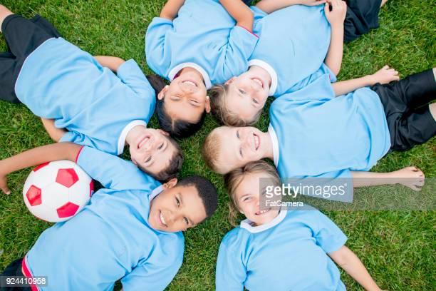 calciatori sdraiati sull'erba - fat soccer players foto e immagini stock