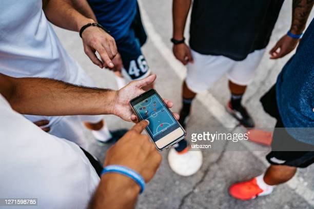 soccer players making strategy on phone - football team stock pictures, royalty-free photos & images