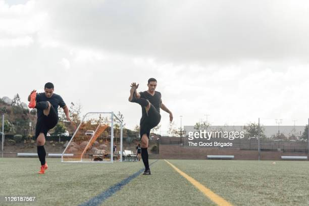 soccer players performing warm up drills on field - warm up exercise stock pictures, royalty-free photos & images