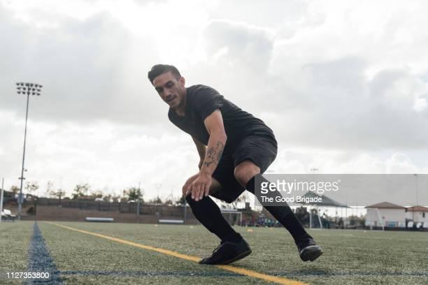 soccer players performing warm up drills on field - sporttraining stock-fotos und bilder