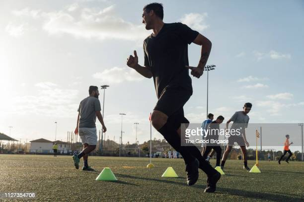 soccer players performing warm up drills on field - sports training drill stock pictures, royalty-free photos & images