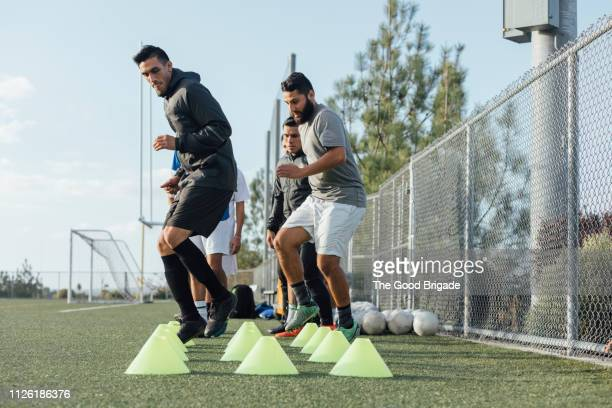 soccer players performing warm up drills - sports training drill stock pictures, royalty-free photos & images