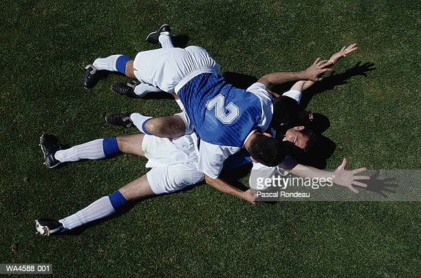 soccer players piling on each other on field in celebration - amateur stock pictures, royalty-free photos & images