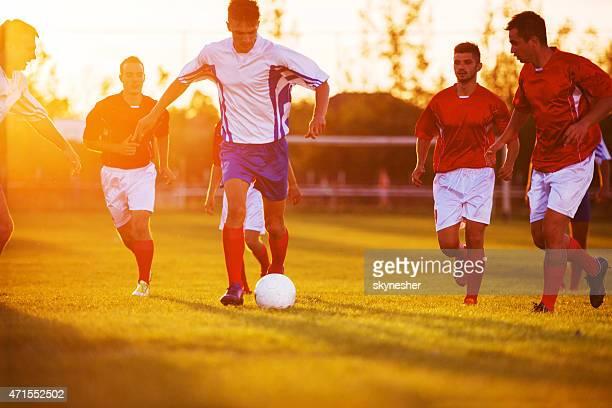 Fußball Spieler spielen Fußball bei Sonnenuntergang.