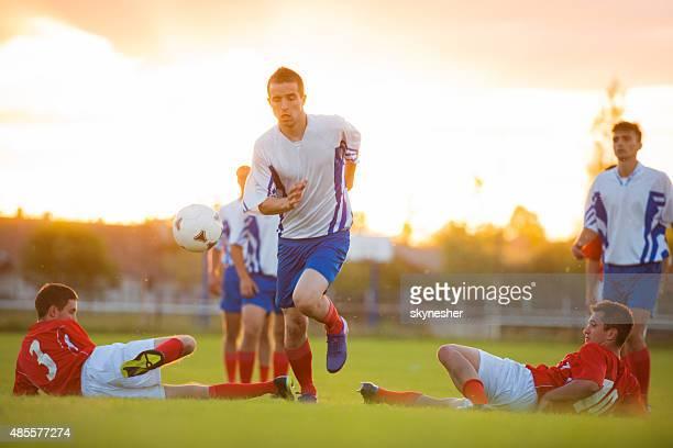 サッカーサッカープレーヤーの夕暮れのトランプます。 - tackling ストックフォトと画像