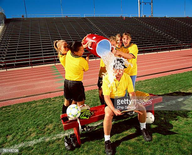 Soccer players pouring water on coach
