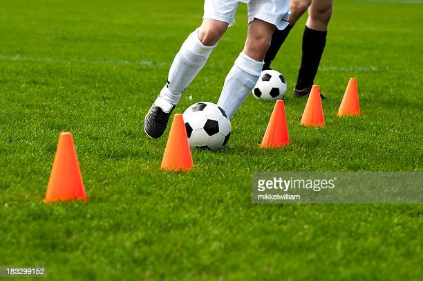 soccer players run with football past cones during training session - cone shape stock pictures, royalty-free photos & images