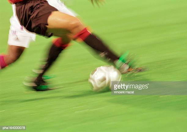 Soccer players running with ball, lower section, blurred.