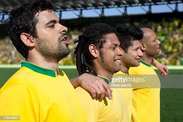 soccer players singing national anthem - national team stock-fotos und bilder