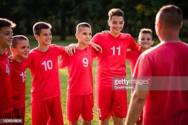 futbolistas de pie y escuchando un entrenador - capitán del equipo fotografías e imágenes de stock