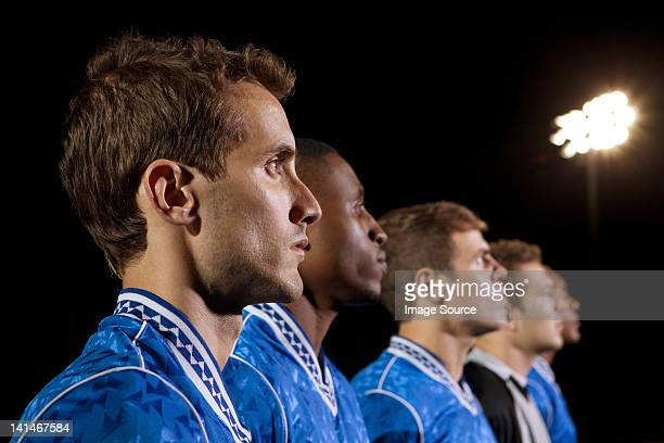 soccer players standing in line on pitch at night - football team stock pictures, royalty-free photos & images