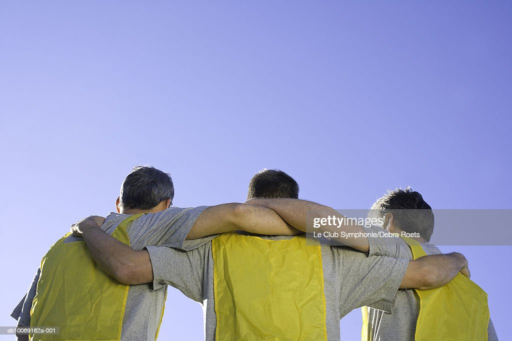 Soccer players standing with arms around each other, rear view : Stockfoto