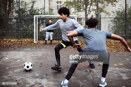 Joueurs de football s'attaquer et défendre dans match