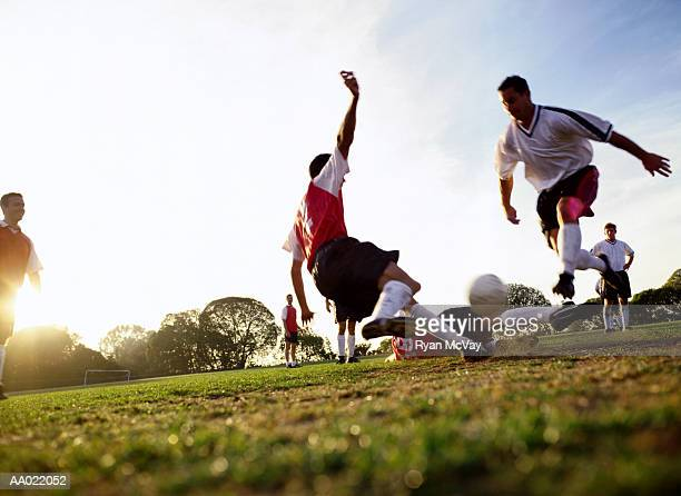 soccer players tackling for ball, ground view - sportlicher zweikampf stock-fotos und bilder