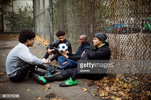 Soccer players talking while sitting against fence