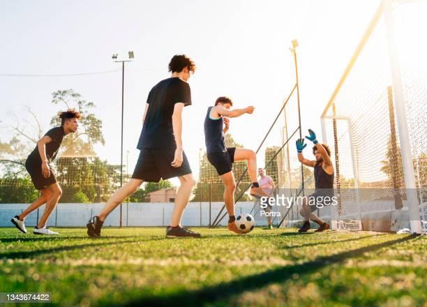 soccer players together at field during sunny day - atacante de futebol imagens e fotografias de stock