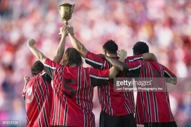 Soccer players triumphantly holding up trophy