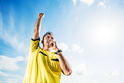 Soccer referee blowing his whistle against the sky. 471552530