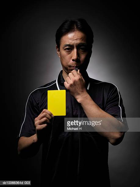 soccer referee blowing whistle and holding yellow card, portrait, close-up - schiedsrichter stock-fotos und bilder
