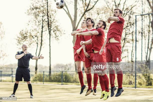 a soccer referee controlling the situation during a football match - soccer referee stock photos and pictures