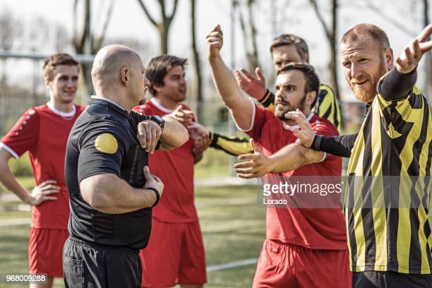 a soccer referee controlling the situation during a football match - yellow card stock pictures, royalty-free photos & images